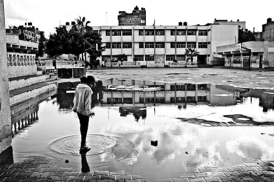 Gaza Beach Camp: Dalia, fille de Shadia et Shadi, marche dans l'eau de la court de l'&eacute;cole apr&egrave;s que des averses soient tomb&eacute;es sur la bande de Gaza. <br /> <br /> Gaza, Beach Camp: Dalia, Shadia and Shadi's daughter, is walking in the water of the courtyard after heavy rains felt on Gaza.