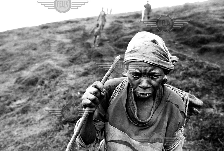 ©Sven Torfinn/Panos Pictures..Eastern Congo, South Kivu province, village Kitoga on the old woman, inhabitant is walking down a hill. because of the war in Congo, people have been leading an isolated life in the mountains of the high plateau, hauts plateaux. little is known about what happened here during the war. That's why international aid organizations now try to get access to the uninviting, inhospitable area..civil war, population