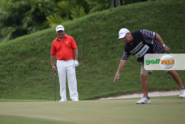 Damien McGrane (IRL) eyes up a birdie putt on the 17th  with the help of caddie Peter Futcher during Round One of the The Championship 2014 from the Laguna National Golf & Country Club, Tampines, Singapore. Picture:  David Lloyd / www.golffile.ie