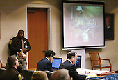 Convicted sniper John Allen Muhammad, seated left, listens to the testimony of his ex-wife Mildred as a photo of him in military camoflage holding an M16 rifle is displayed on a screen in the penalty phase of his trial in Virginia Beach Circuit Court in Virginia Beach, Virginia on November 19, 2003.   Now in the punishment phase of the trial, the jury can only choose execution or life in prison without parole for Muhammad, who was found guilty Monday, November 17, 2003 of all charges, including two capital murder counts, in one of 10 fatal shootings that terrorized the Washington, D.C., area in 2002. <br /> Credit: Tracy Woodward - Pool via CNP