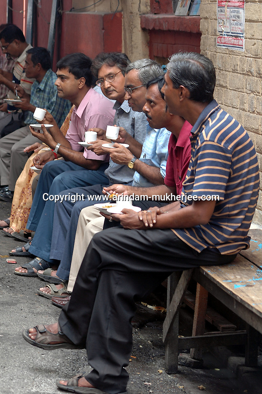 Office workers having tea during break at  a street food stall at Decker's lane of Kolkata. Street food stalls are serving the office goers for decades. All kind of Indian foods are available on the street at an affordable price. They sale them openly. Street food stalls are another results of unempoloyment and over poppulation. They serve millions of people in India. Kolkata, West Bengal,  India  7/18/2007.  Arindam Mukherjee/Landov
