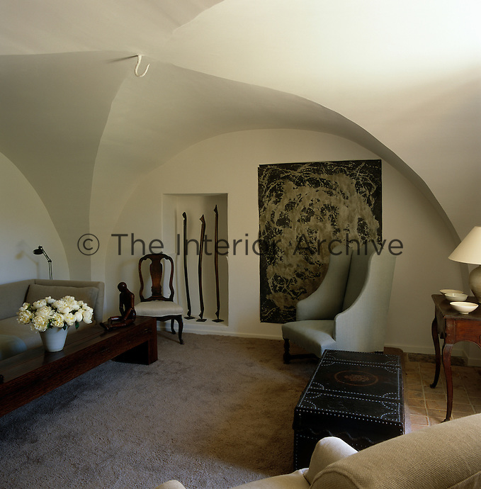 A large painting and a wooden sculpture in a niche are the only embellishments in the simple living room