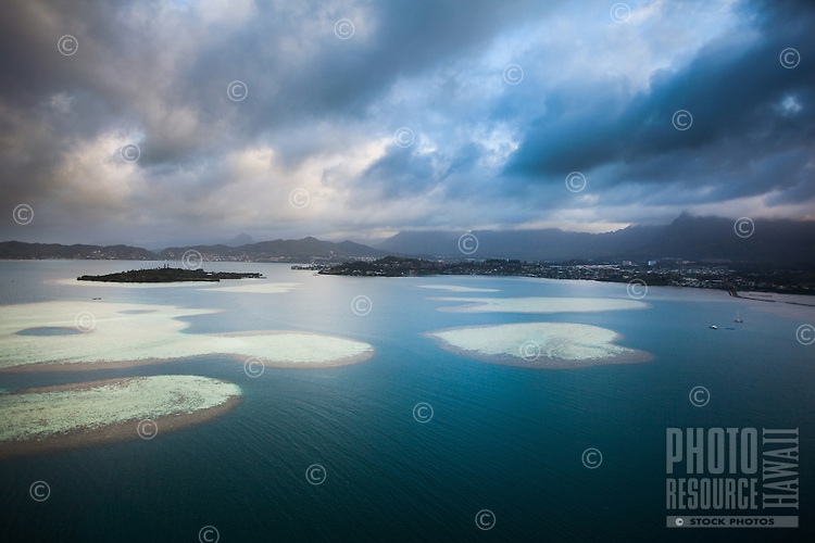 An aerial view of the Kane'ohe Sandbar on an overcast day; in the distance, clouds cover the top of the Ko'olau Mountain Range on O'ahu.