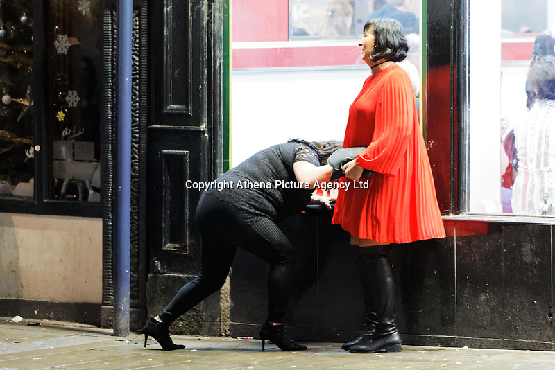 A woman is assisted by her friend to stand up in Wind Street, Swansea, Wales  on Mad Friday, Booze Black Friday or Black Eye Friday, the last Friday night before Christmas Day, when traditionally people in the UK go out to celebrate the start of their holidays. Friday 22 December 2017