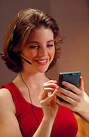 A smiling young woman talking on a telephone headset and working with a Palm Pilot.