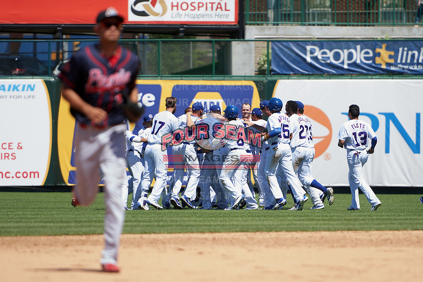 South Bend Cubs Alberto Mineo (47) is mobbed by teammates, including Matt Rose (17), Andruw Monasterio (6), Eddy Martinez (15), Eloy Jimenez (27), Bryant Flete (13), after a walk off base hit during the first game of a doubleheader against the Peoria Chiefs on July 25, 2016 at Four Winds Field in South Bend, Indiana.  South Bend defeated Peoria 9-8.  (Mike Janes/Four Seam Images)