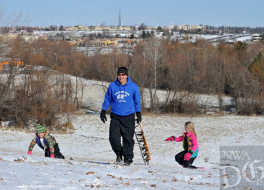 NWA Democrat-Gazette/Michael Woods --03/05/2015--w@NWAMICHAELW... Davey Bryan of Fayetteville helps carry a sled up the hill for his daughter Chloe Bryan, age 8 (right) and his niece Lily Mikesch, age 6, as they enjoy a morning of sledding down the hill behind Christian Life Cathedral Thursday morning  in Fayetteville.  Winter weather caused schools and many local businesses to close down for a second day in a row.