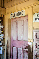 Old rustic faded red door with Post Office sign above at the iconic Bainham Store in Golden Bay, South Island, New Zealand - stock photo, canvas, fine art print