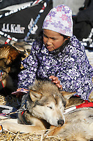 Young Angelina Hamilton pets Dallas Seavey's dog Derby as he rests on straw at the Shageluk village checkpoint during the 2011 Iditarod race..