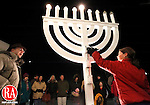 "Southbury, CT- 08, December 2010-120810CM01 Anna Pekovich, 10, of Middlebury (right) lights the Menorah Wednesday night at B'Nai Israel of Southbury. Leading the celebration is Rabbi Eric Polokoff (left).  ""We have wanted an outdoor Menorah for some time. In introducing our Chanukah Festival in the talmud, our Rabbi's taught that it is incumbent to place the Chanukah lamp by the door of one's house on the outside. For the goal was to publicize the miracle."" said Rabbi Polokoff, with Wednesday night marking the final night of Hanukkah. The Menorah was constructed by synagogue member, Mike Pekovich.  Christopher Massa Republican-American"