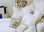 A detail of a traditional neutral bedroom with double bed embroidered and lace cushions