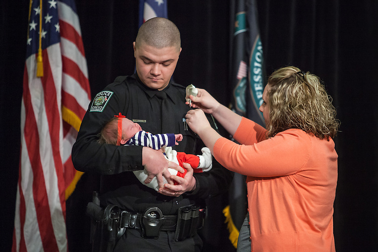 Ohio University Police Officer Justin Boggs is pinned with his new badge by his wife Tari while he holds their newborn Carleigh Mae Boggs.  The event gave an opportunity to honor not only the officers but their families that make up their larger community among the University police. Photo by Ohio University / Jonathan Adams