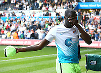 Yaya Toure of Manchester City covers his eyes as he throws his shirt into the crowd during the Barclays Premier League match between Swansea City and Manchester City played at The Liberty Stadium, Swansea on 15th May 2016