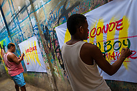 """Colombian sign painters write with a brush while working on music party posters in the sign painting workshop in Cartagena, Colombia, 17 April 2018. Hidden in the dark, narrow alleys of Bazurto market, a group of dozen young men gathered around José Corredor (""""Runner""""), the master painter, produce every day hundreds of hand-painted posters. Although the vast majority of the production is designed for a cheap visual promotion of popular Champeta music parties, held every weekend around the city, Runner and his apprentices also create other graphic design artworks, based on brush lettering technique. Using simple brushes and bright paints, the artisanal workshop keeps the traditional sign painting art alive."""