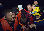 Refugees disembark at night from a private fishing boat that rescued them at sea, bringing them into the harbor at Skala Sikaminia, on the Greek island of Lesbos, on November 1, 2015. They were received in Greece by local and international volunteers, then proceeded on their way toward western Europe.