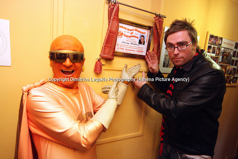 Pictured L-R: Captain Beany with tv personality Danny Wallace unveiling a commemorative plaque.<br /> Pictured: Captain Beany in his museum.<br /> Re: Captain Beany (aka Barry Kirk) founder of the first Bean Museum of Excellence in a council flat in Port Talbot, south Wales.<br /> Caped crusader Captain Beaney has converted his welsh flat home into a historical tribute to the humble baked bean.<br /> The museum is made up of collectibles and artefacts Captain Beaney has acquired over the years.