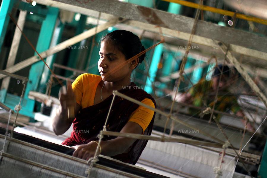 Bangladesh. A woman weave the silk with a machine to make clothes. .Most of the silk produced by BRAC's beneficiaries is bought up by the Manikganj Foundation where the silk is dyed, and block printed and finally tailored into expensive kurtas and saris that are then sold through BRAC's sister-concern - the high-end designer store Aarong - which means bazaar. This is the final stage of a long process that began with the women who raise the silk-worms. ..Bangladesh. Une femme tisse à l'aide d'une machine la soie pour confectionner des vêtements..La plupart de la soie produite par les bénéficiaires du BRAC est acheté par la Fondation Manikganj où la soie est teinte, puis imprimée en block et finalement taillée en de chers kurtas et saris qui sont ensuite vendus par le reseau de vente du BRAC, le Aarong. C'est l'étape finale d'un long processus qui a commencé avec des femmes qui élevent des vers à soie.