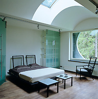 A Japanese-style bed with a contemporary twist in a bedroom with a circular window and a skylight