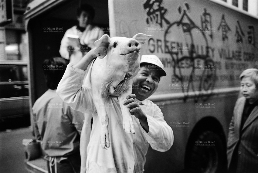 USA. New York City. Chinatown. A smiling chinese man carries a dead pig on his shoulder. 11.10.1985 © 1985 Didier Ruef