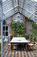 A conservatory extension has a tiled floor and a large marble-topped table
