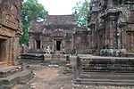 Angkorian temple Banteay Srei (late 10th century) 967.<br /> Northern library showing Krishna killing Kamsa on the pediment. Gaurdians and open doorway into Mandapa at centre with pediment showing Kubera, God of Wealth here appearing in his capacity as gaurdian of the north.Northern tower sanctuary on right of picture.<br /> Banteay Srei temple hthree sanctuary towers.The central sanctuary and the southern sanctuary were dedicated to Shiva and the northern sanctuary was dedicated to Vishnu.<br /> Banteay Srei temple is situated 20km north of Angkor, built during the reign of Rajendravarman by Yajnavaraha, one of his counsellors. In antiquity Isvarapura was a small city that grew up around the temple. Banteay Srei was dedicated to the worship of Shiva, the foundation stele describes the consecration of the linga Tribhuvanamahesvara (Lord of the three worlds) in 967.