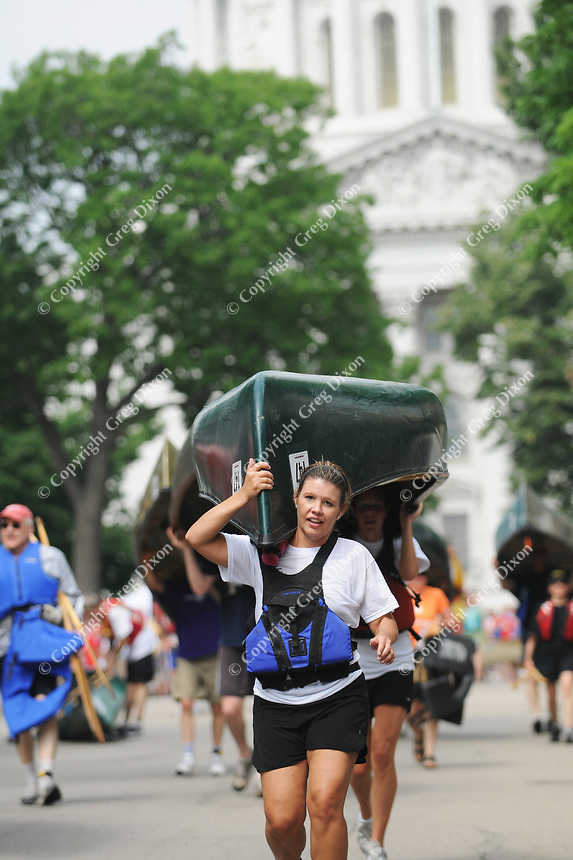 Athletes complete the second leg of Paddle & Portage by carrying their canoes and kayaks around the Capitol Square on Saturday in Madison