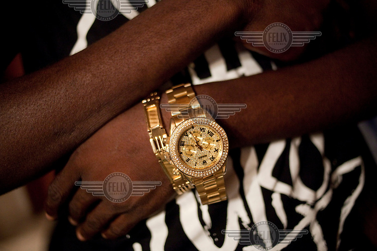 A gold Rolex watch on the wrist of one of a group of friends at a home in a new housing estate called Lekki Phase Three. The home owner spent years abroad for university, a masters degree and work, before returning to Lagos. Lekki Phase Three is the third housing area to be built extending out from Victoria Island, one of the wealthier areas of the city.