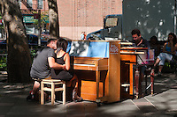 New York, NY -  2 July 2010 - Play Me I'm Yours. Back to back piano playing in TriBeCa Park. A couple shares a romantic moment at the keyboard.