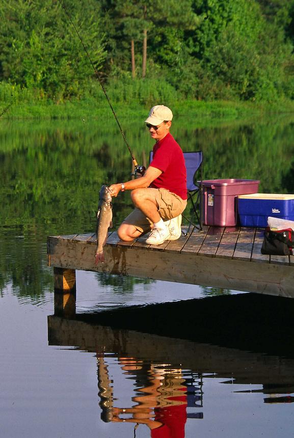 Angler on dock landing channel catfish, Barksdale Lake, Arkansas