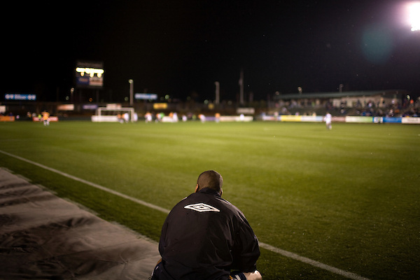 """March 14, 2009. Cary, NC.. The Carolina Railhawks went home in foul weather with a  1-0 victory over the New England Revolution of the MLS, in the inaugural """"Community Shield"""" match and their first professional outing under new coach, Martin Rennie. . A player watches the action form the sideline."""