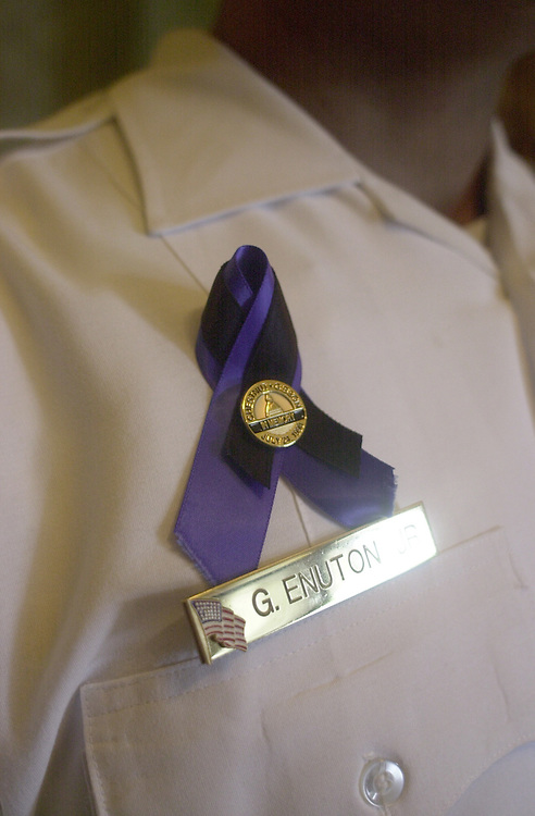 Memorial.1(TW)072400-- Officer George Enuton Jr. wears a memorial ribbon in honor of officers' Chestnut and Gibson that he has had since the original memorial service in 1998.