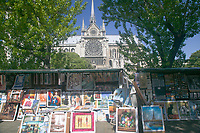 Book stalls of Les Bouquinistes on Quai de Montebello on the left bank of the Seine River with Notre Dame in the background in Paris, France.