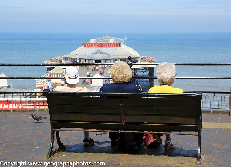 People looking out to sea above the pier at Cromer, Norfolk, England, UK