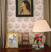 A miniature chair and family snapshot sit on a chest of drawers in the bedroom which has been wallpapered in Colefax and Fowler's 'Bowood'