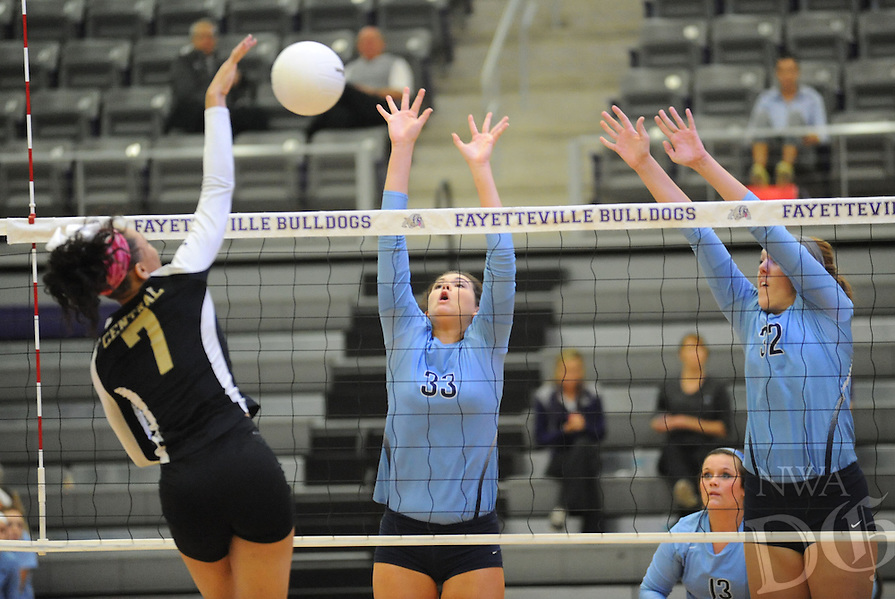 STAFF PHOTO ANDY SHUPE - Kiara Williams (7) of Little Rock Central sends the ball over the net as Lauren Law (33) and Kimberly Huff (32) of Har-Ber defend during play Tuesday, Oct. 28, 2014, in the Class 7A state tournament at Fayetteville High School.