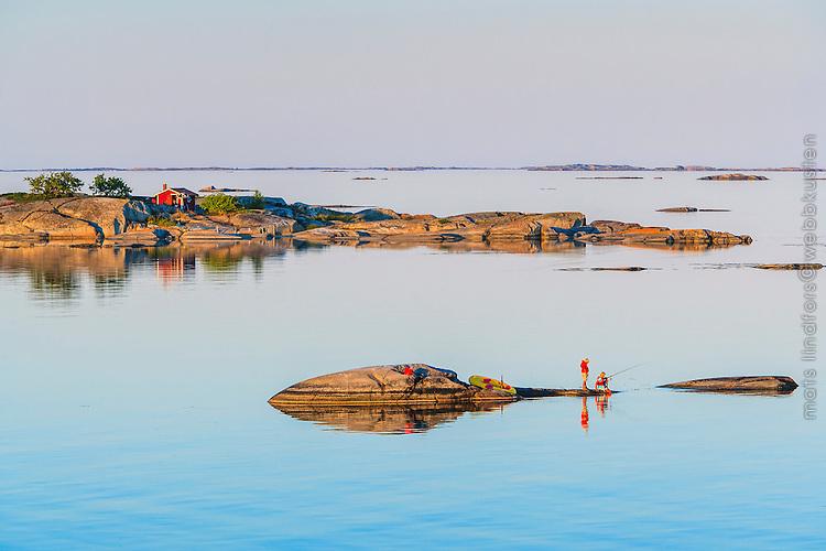 Barn på skär som fiskar vid Kallskär i Roslagen Stockholms skärgård med spegelblanka fjärdar. / Archipelago Stockholm Sweden