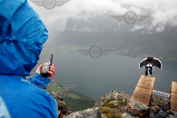 Communication is essential, not only for starting the jumpers but also to keep everyone informed about shifting weather conditions. World BASE Race held in Innfjorden, Norway, where BASE jumpers in wingsuits compete in flying down the mountain. The winner is called the World's Fastest Flying Human Being..©Fredrik Naumann/Felix Features.