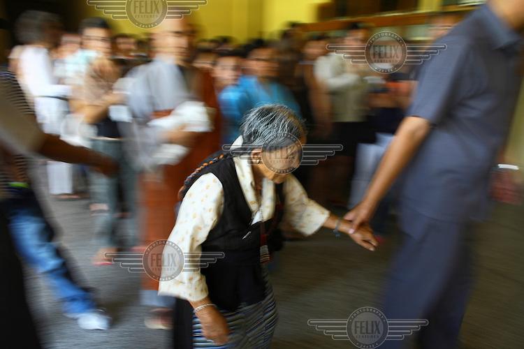 An elderly woman is led to meet the Karmapa at the Gyuto Tantric Monastic University.