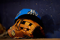 A Hudson Valley Renegades hat rests on a glove in the dugout during a game against the Connecticut Tigers on August 20, 2018 at Dodd Stadium in Norwich, Connecticut.  Hudson Valley defeated Connecticut 3-1.  (Mike Janes/Four Seam Images)
