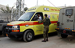 Israeli soldiers gather around an ambulance at the scene where a Palestinian, who according to the Israeli military attempted to stab a soldier, was shot dead, near a check point of the Israeli settlement of Kiryat Arba in the the West Bank city of Hebron on September 3, 2018. Photo by Wisam Hashlamoun
