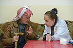 Yusef Gorges, a 66-year old internally displaced Christian, talks with Dr. Kholod Hazim during the visit of a mobile clinic to the village of Sharafiya, Iraq, which was flooded with displaced families when the Islamic State group took over nearby portions of the Nineveh Plains in 2014. The clinic is a program of the Christian Aid Program Nohadra - Iraq (CAPNI).