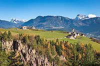 Italy, Alto Adige - Trentino (South Tyrol), Renon: view across the earth pyramides (Hoodoos), village Monte di Mezzo with church St. Nikolaus (built 1200) towards the Dolomites with Sassolungo (Langkofel), Sasso Piatto (Plattkofel) and Sass Rigais (Geislerspitzen) mountains   Italien, Suedtirol (Alto Adige-Trentino), Ritten: Blick ueber die Erdpyramiden und Mittelberg am Ritten mit der St. Nikolauskirche (erbaut um 1200) in die Dolomiten mit Langkofel, Plattkofel und die Geislerspitzen (links)