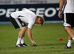 Stuart McCall pulls a divot out of the pitch before the match as concern grows over the state of the playing surface in Skopje