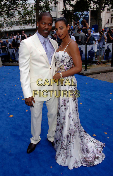 "JAMIE FOXX & GUEST.European film premiere""Miami Vice"".Odeon cinema Leicester Square.27th July 2006 in London, England.Ref: FIN.full length white suit floral print dress.www.capitalpictures.com.sales@capitalpictures.com.©Steve Finn/Capital Pictures."