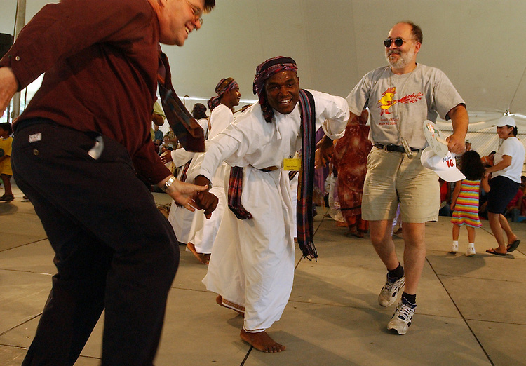 Naain Al-Risadi performs a traditional Lewah dance, with David Lee, left, and an unidentified man, in the Oman dance stage, at the Smithsonian Folklife Festival, Thursday, on the Mall.