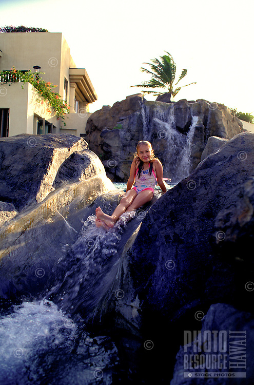 A young girl in a bathing suit sits on top of a rock waterfall at Kona Village Resort on the Big Island of Hawaii.