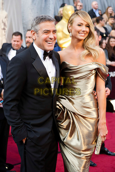 George Clooney, Oscar®-nominee for Performance by an Actor in a Leading Role and Adapted Screenplay, and Stacy Keibler .Arrivals at the 84th Annual Academy Awards® in Hollywood, CA., USA..February 26, 2012.*Editorial Use Only*.oscars half length dress black tuxedo gold silk satin off the shoulder couple .CAP/A.M.P.A.S./NFS.©A.M.P.A.S. Supplied by Capital Pictures.