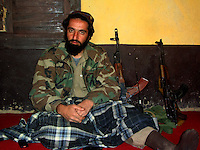 A commander from the Wardak Mobile Patrol Unit sits with several AK47 Kalashnikovs at his side