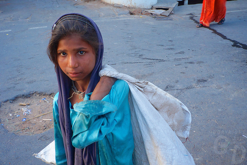 A young girl is collecting garbage in the streets of Pushkar, where poverty prevails. India