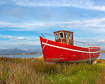 County Galway, Ireland: Red fishing boat in the grasses of Bertraghboy Bay near the village of Roundstone with mountains of the Connemara in the distance